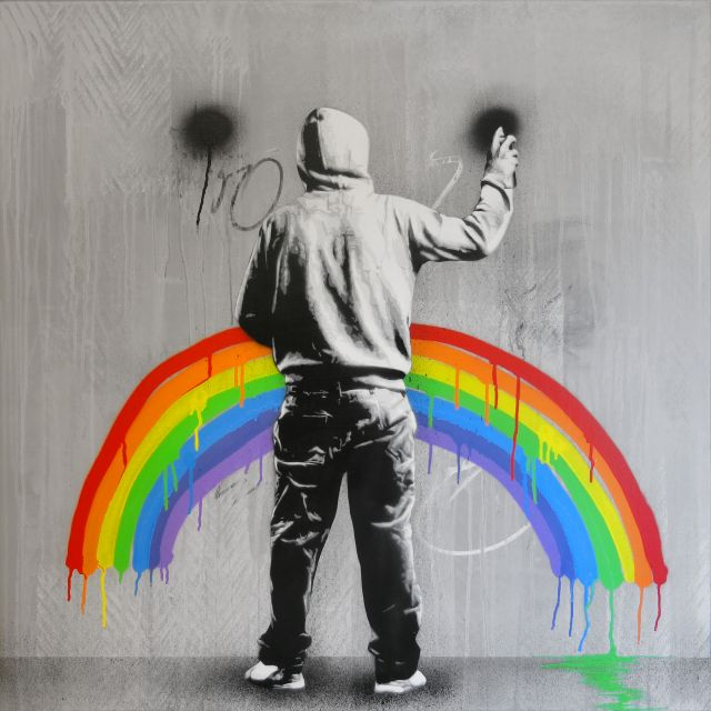 Guy with hoodie painting a rainbow