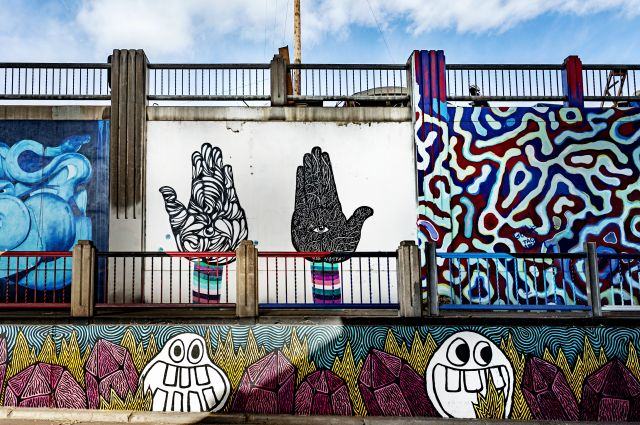 Untitled (collection of three murals: black and white hands facing up, red and blue organic lines, silly faces below)